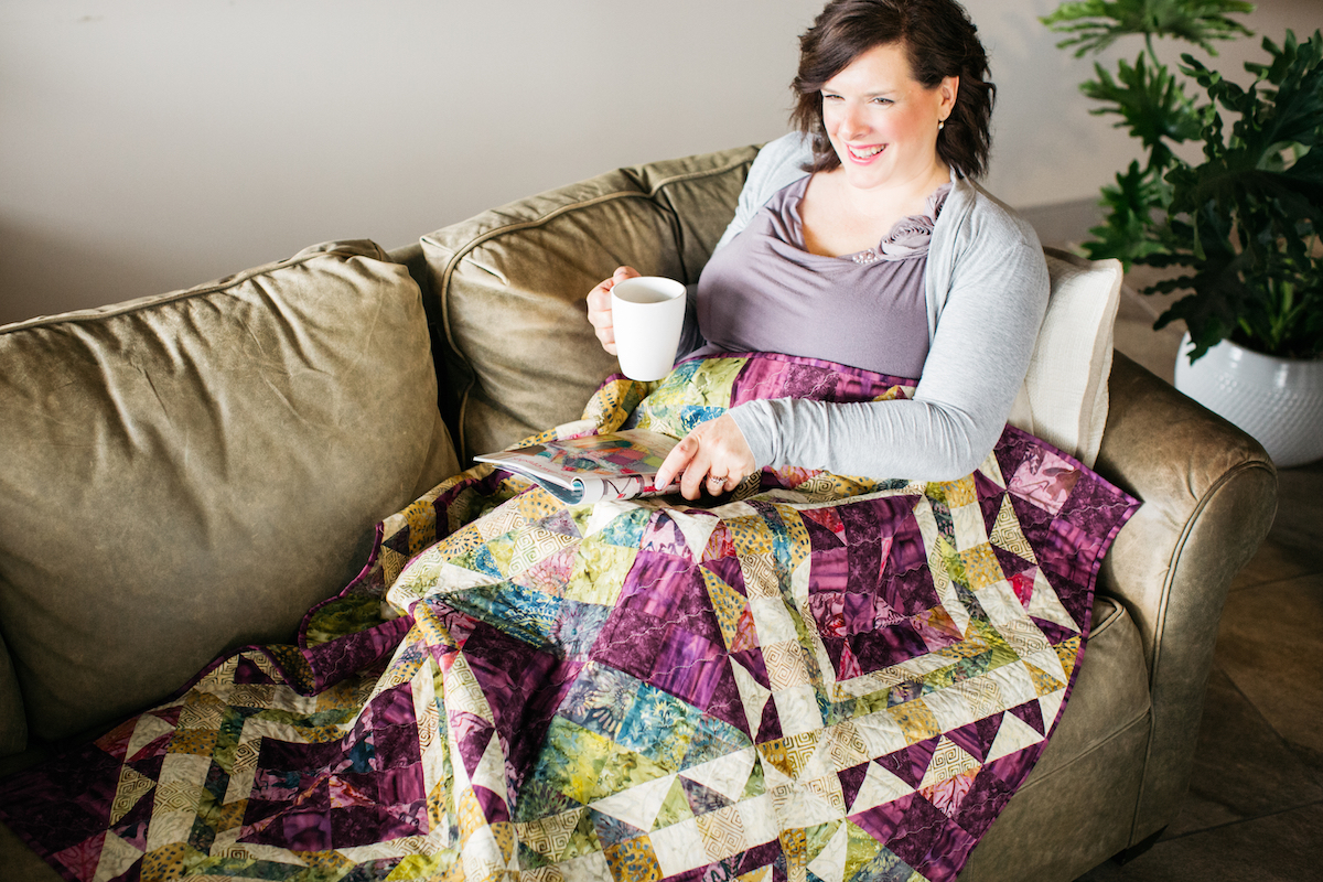 woman on couch with purple quilt with mug