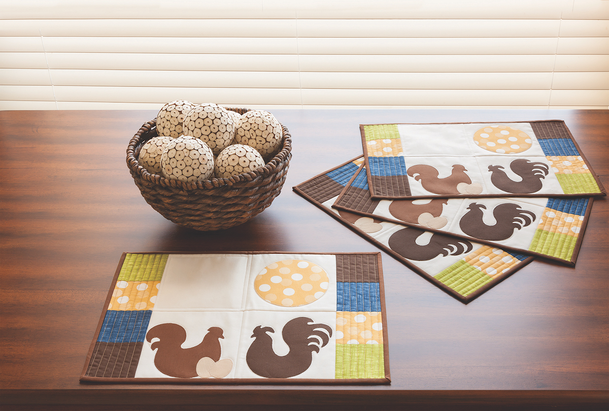 Rooster and egg applique on quilted placemats with lime, yellow, brown and blue patches on a wooden table.