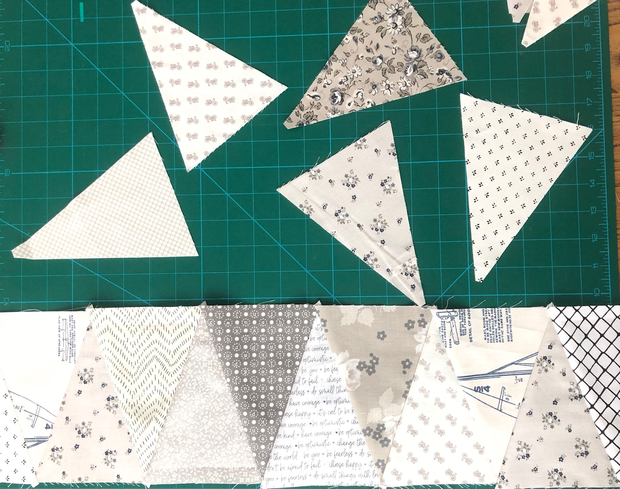 fabric cut into equilateral triangles on a self-healing cutting mat above a row of equilateral triangles sewn together into a rectangle