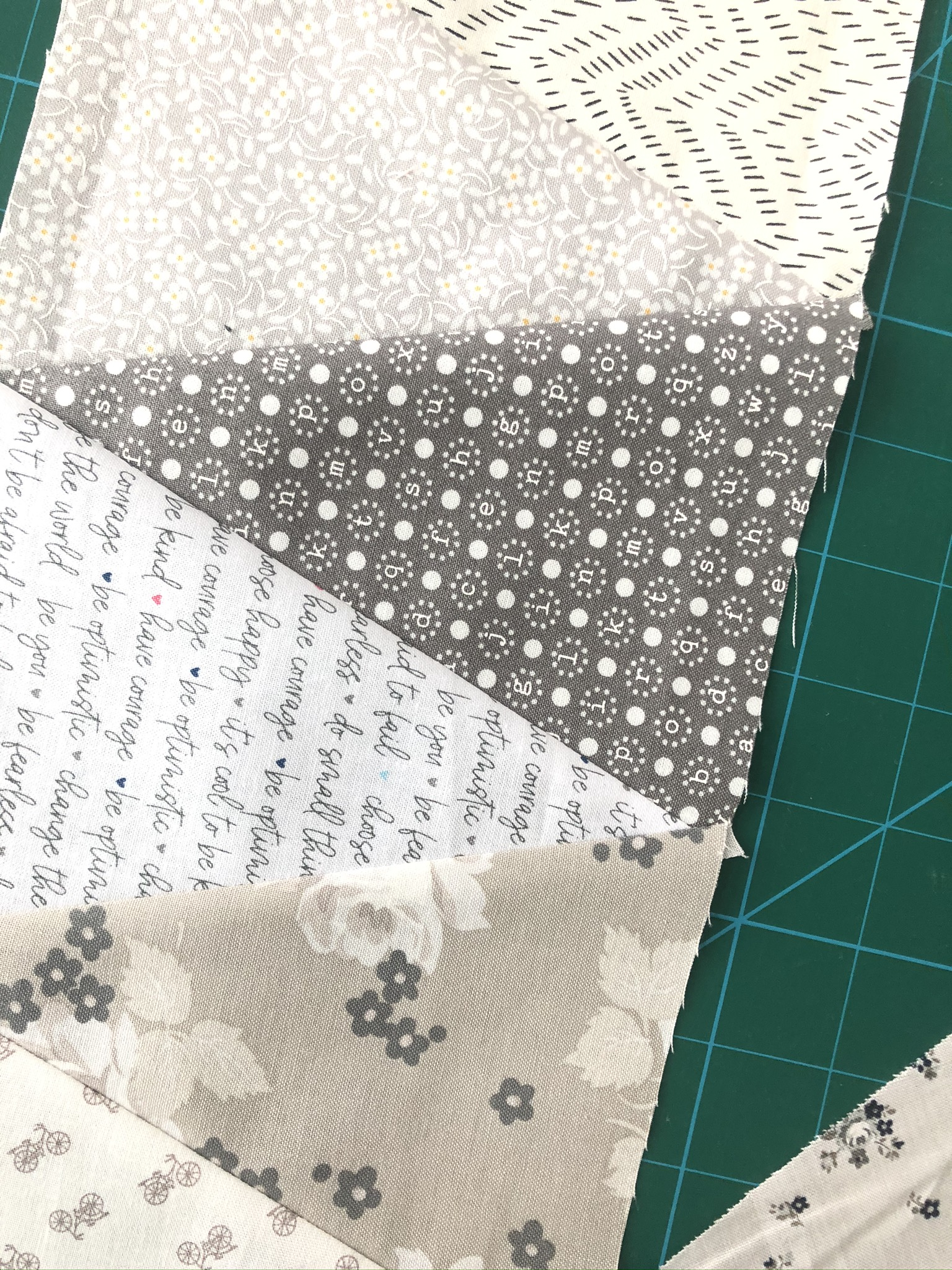 close up of low volume grey, white, cream and taupe fabric equilateral triangles