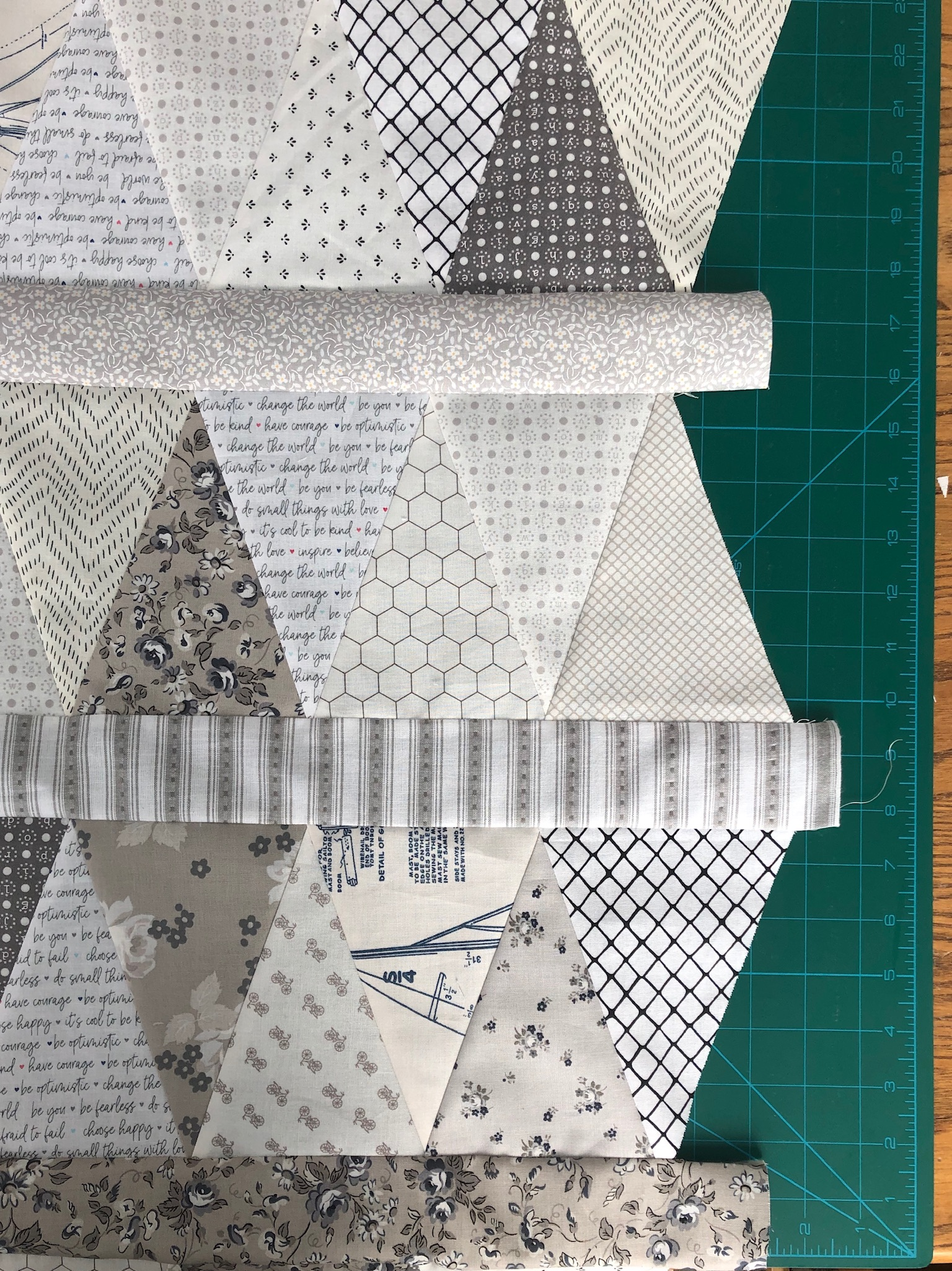 low volume fabric equilateral triangles sewn in rows with sewn sashing between each rectangular row