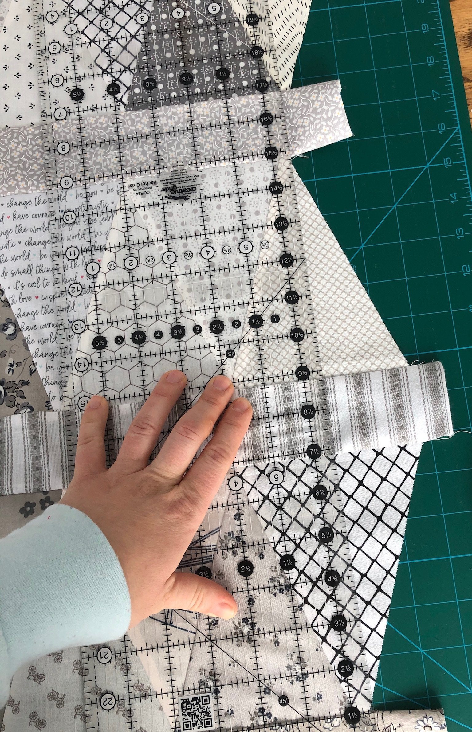 hand over low volume equilateral triangle quilt with an acrylic quilting ruler used to measure a straight edge on the uneven quilt