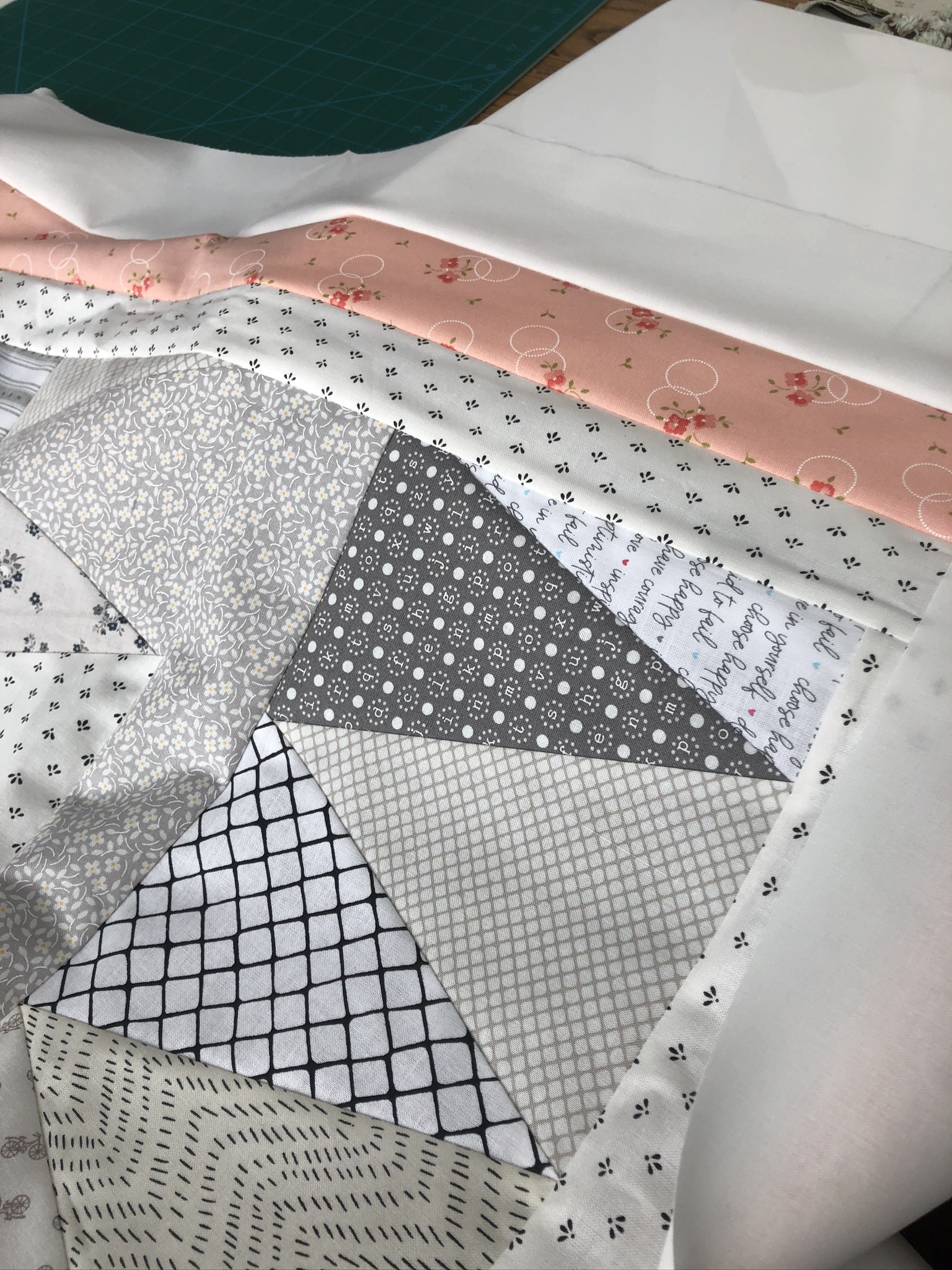 close up of low volume equilateral triangle quilt pieced with sashing and a triple border of white and pink and grey printed fabrics