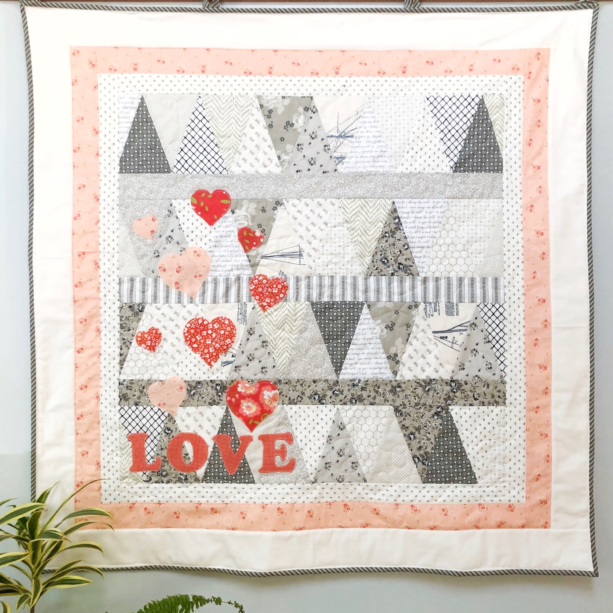 full view of low volume valentine's pennant quilt with heart and the word love appliqued in the lower right corner hanging on a wall