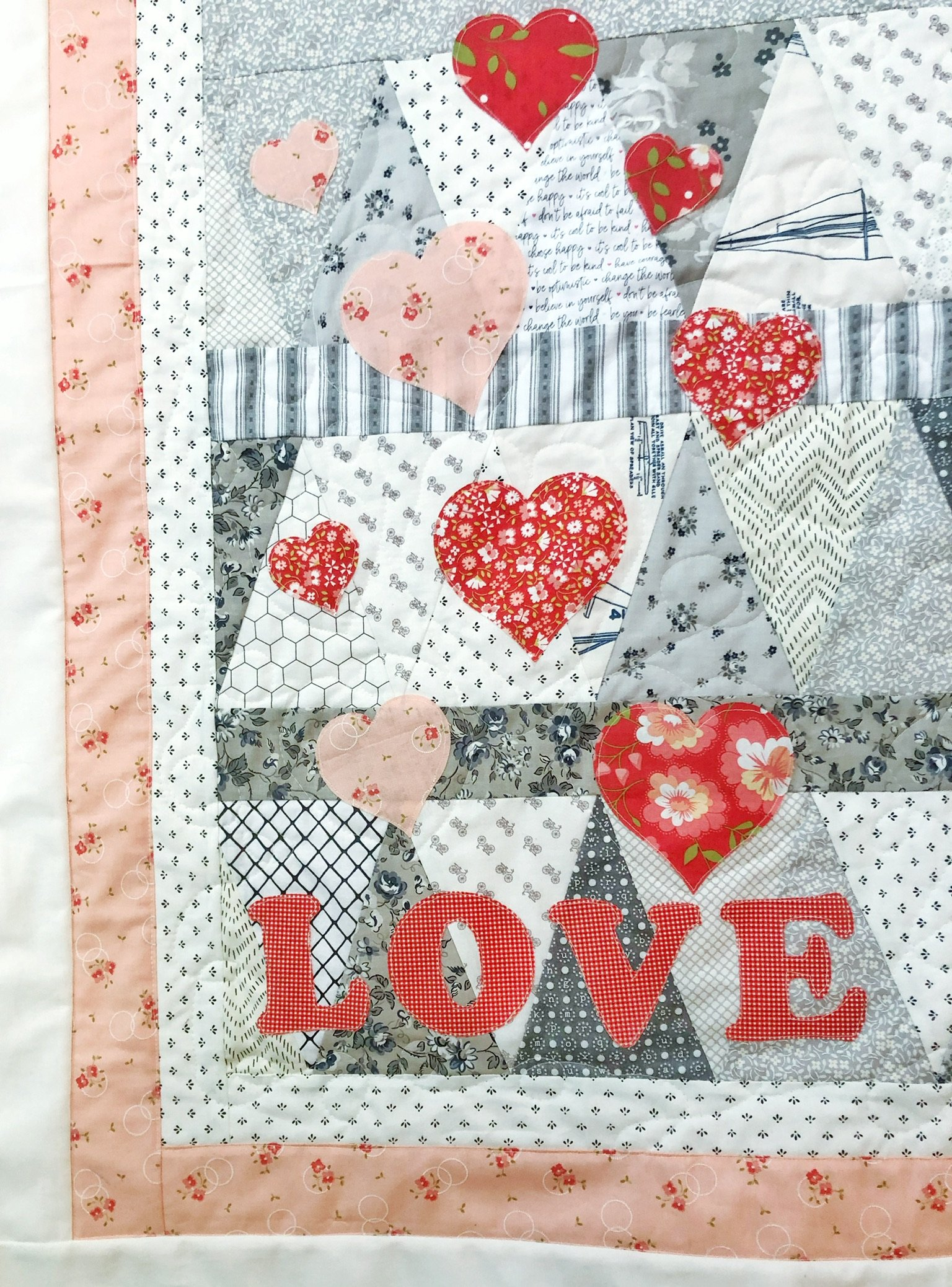 close up of quilted wall hanging with a triple border and pink and red heart appliques and the word love