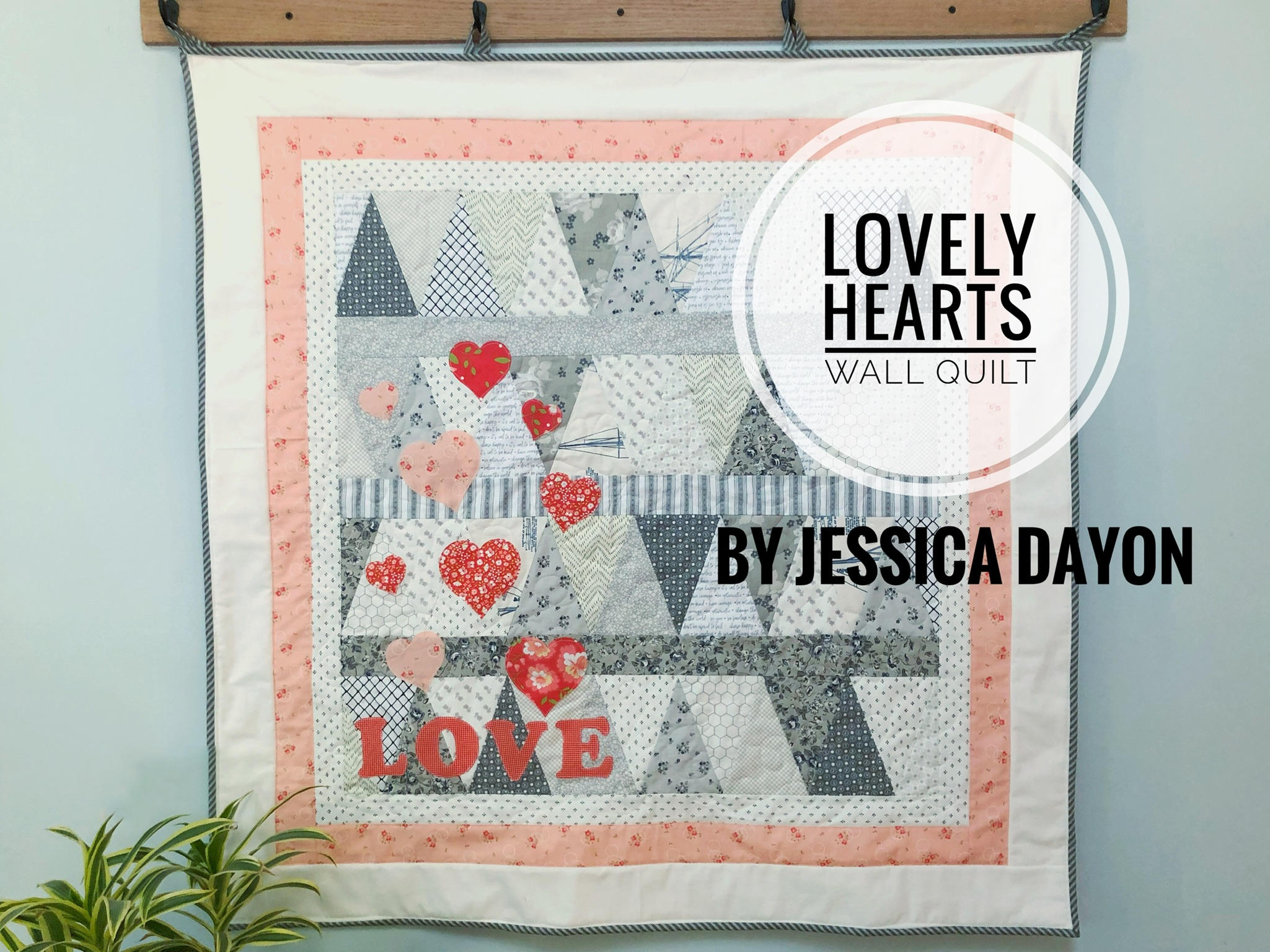 peach grey and white quilted wall hanging made of equilateral triangles and featuring love heart shapes and the word love