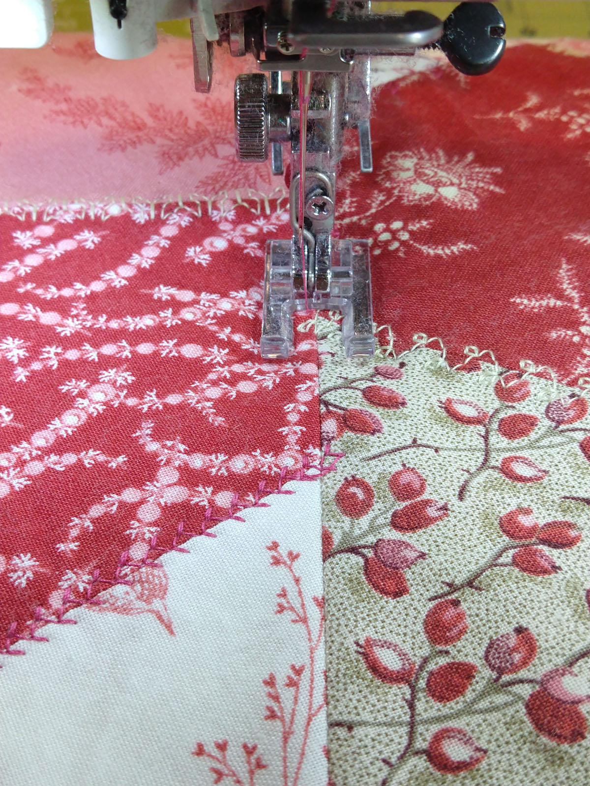 open to sewing machine foot stitching quilt pieces