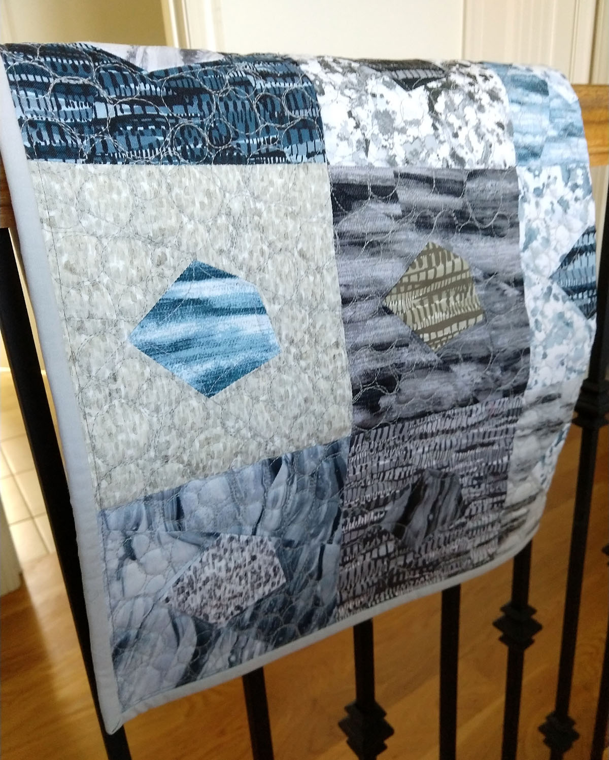 GO Crazy Quilt block quilt finished and hung over a rod iron stair rail