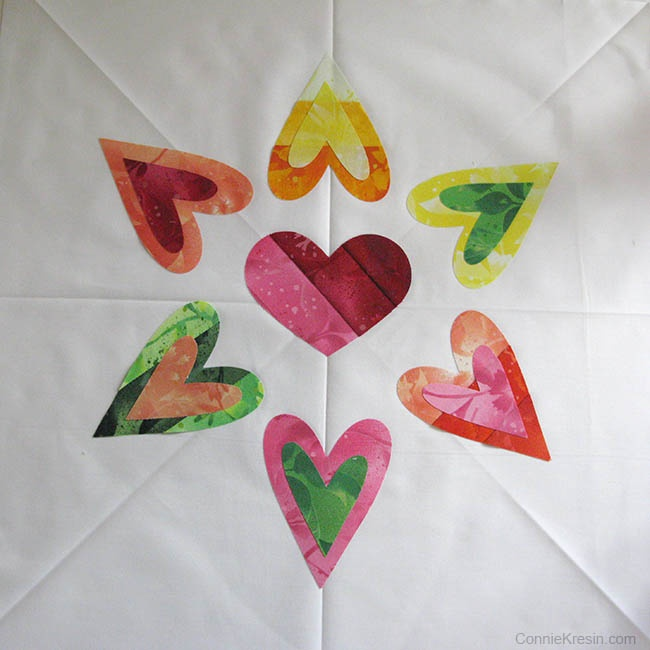 Placing the AccuQuilt Queen of Hearts applique on pillow top