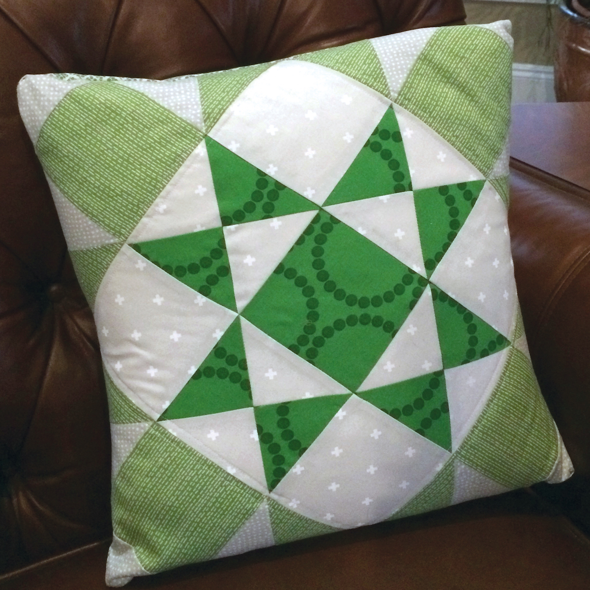 green and white Ohio star quilt block throw pillow on a leather chair