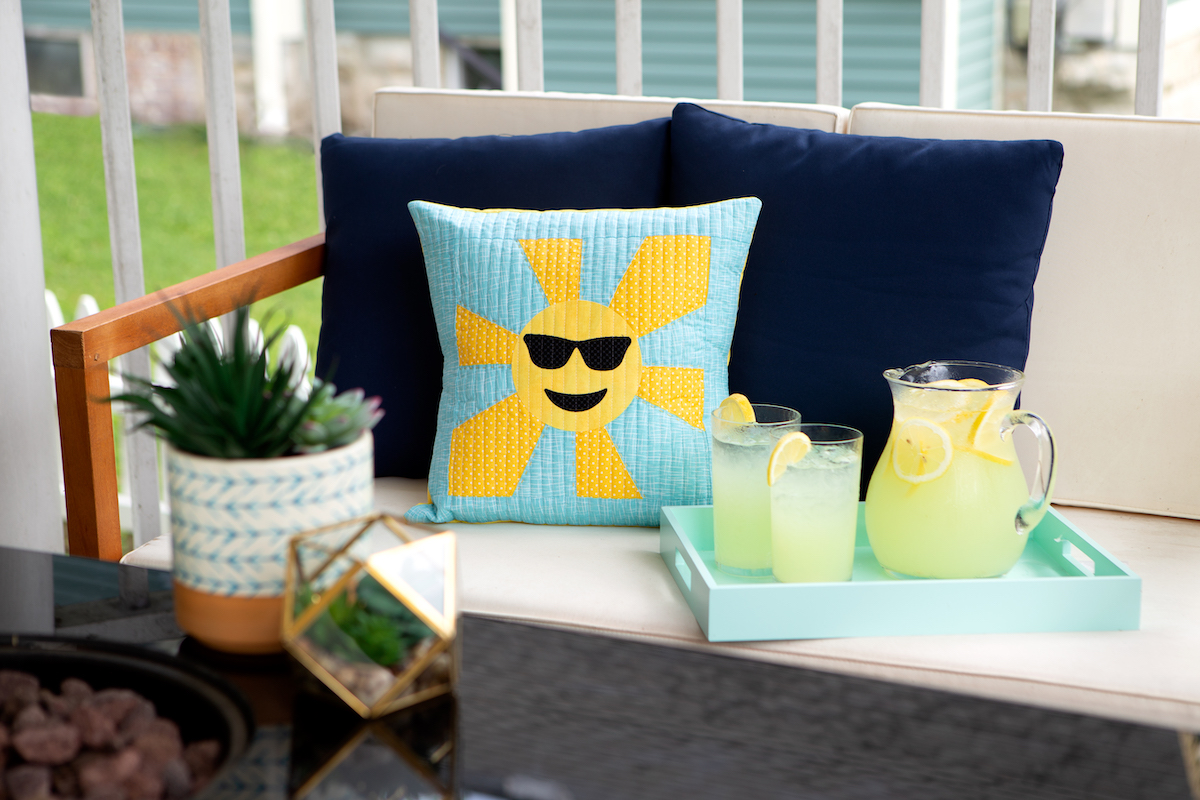 Teal and yellow sun throw pillow on outdoor bench with teal tray and pitcher of lemonade.
