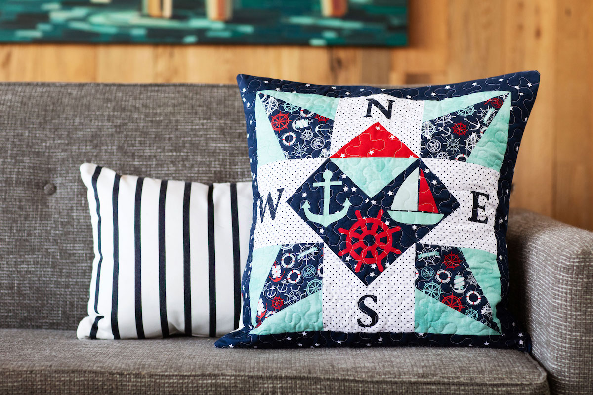 Nautical-inspired compass throw pillow next to striped pillow on grey couch.