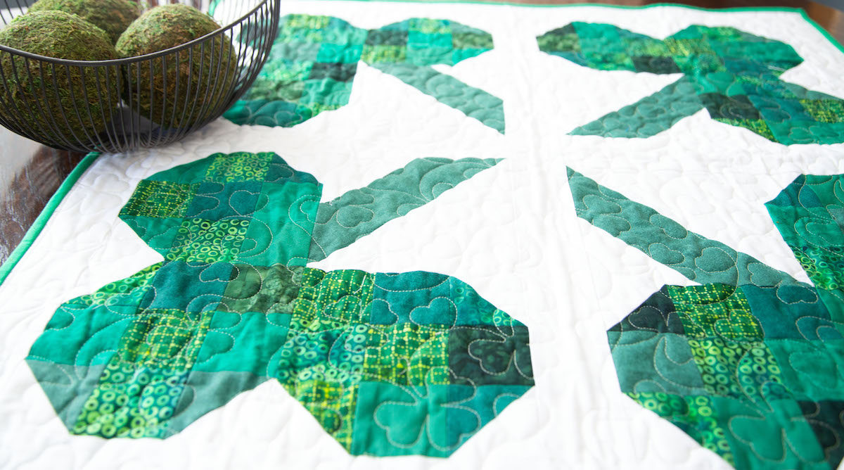 four leaf clover quilted table topper on a wooden table with a bowl of moss balls