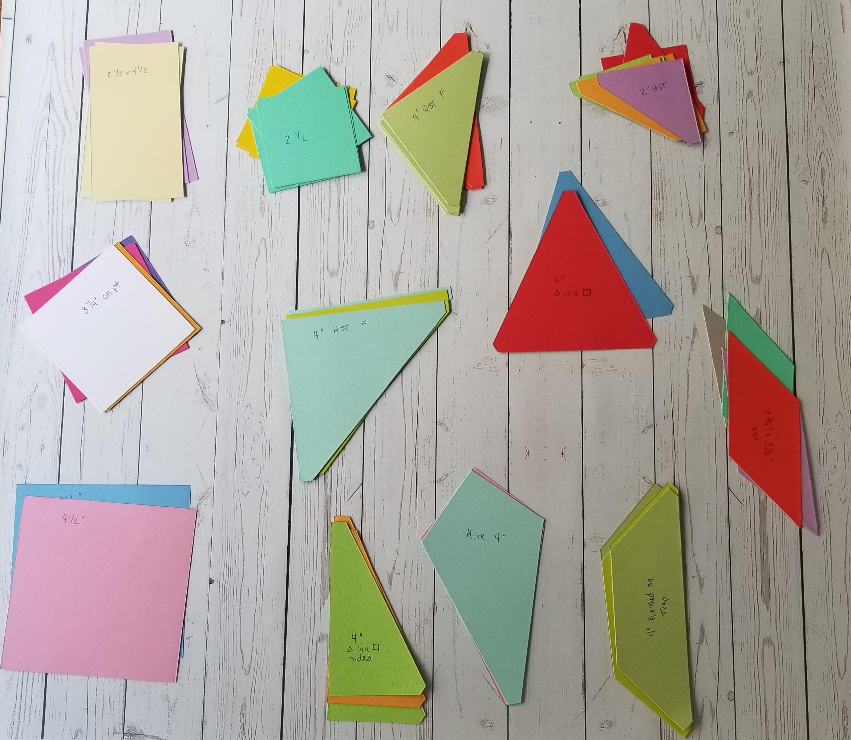 Multicolored cardstock shapes with on wood backdrop
