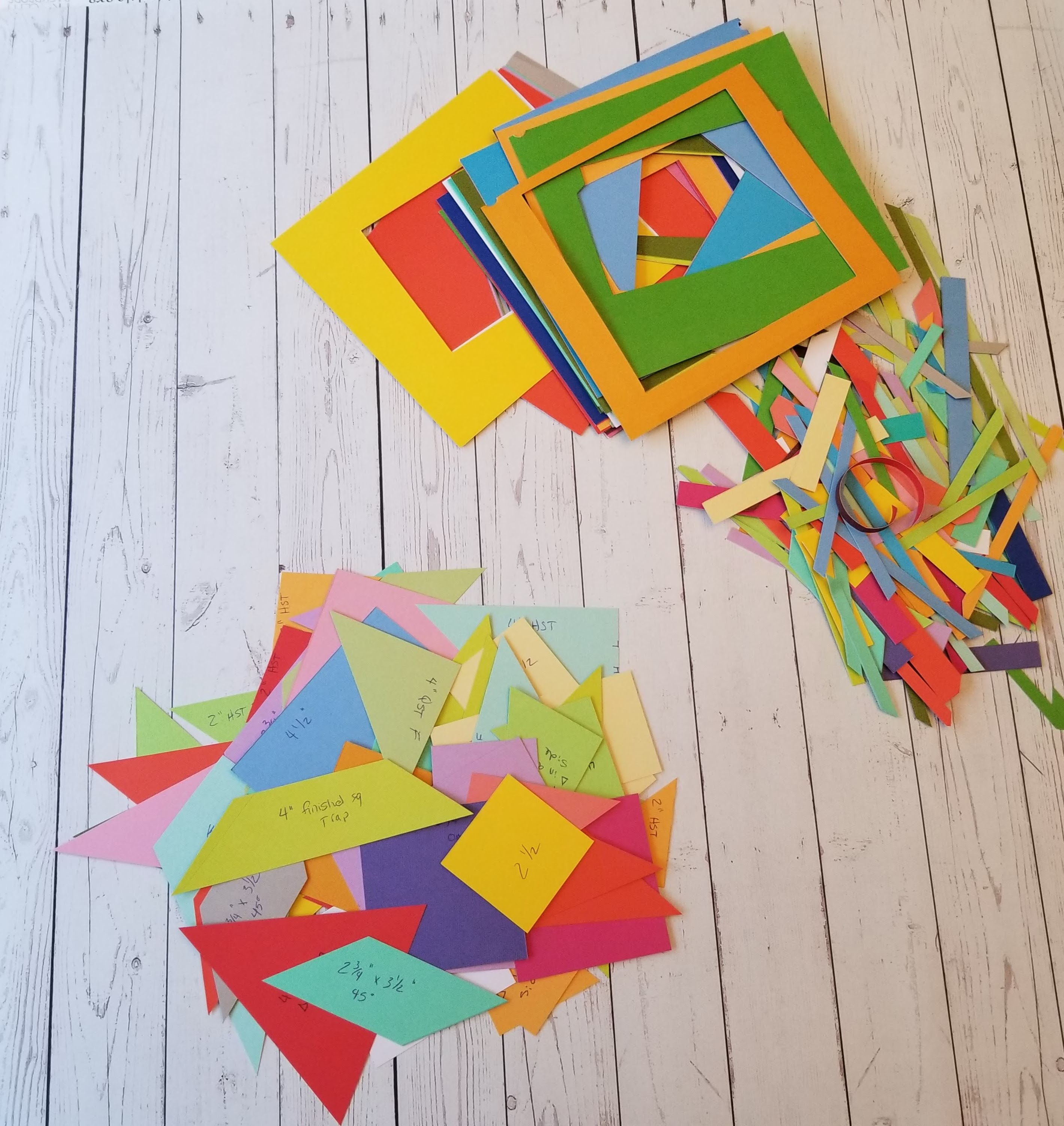 Multicolored shapes next to paper scraps on wood backdrop