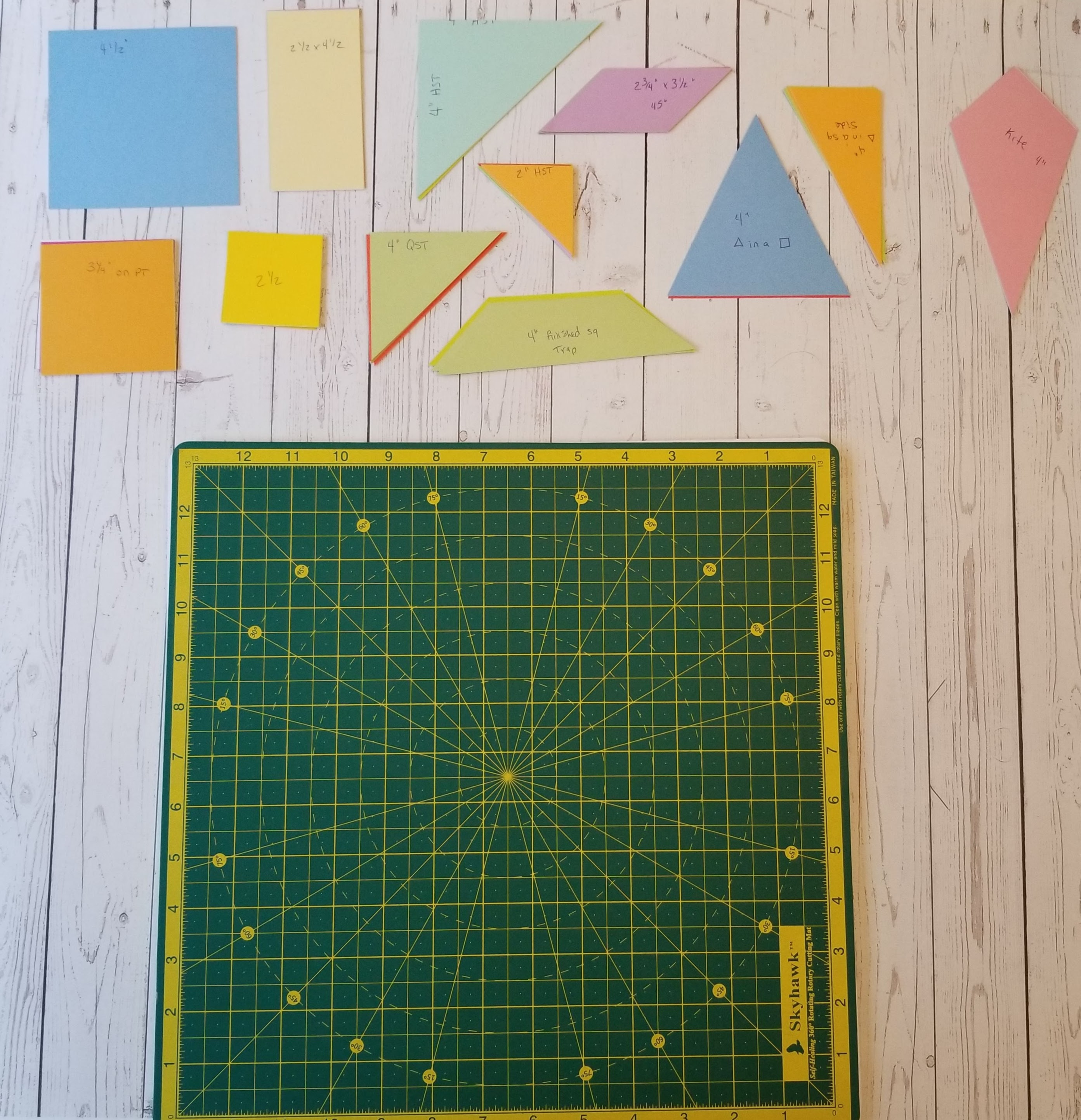 Multicolored paper shapes next to self healing cutting mat