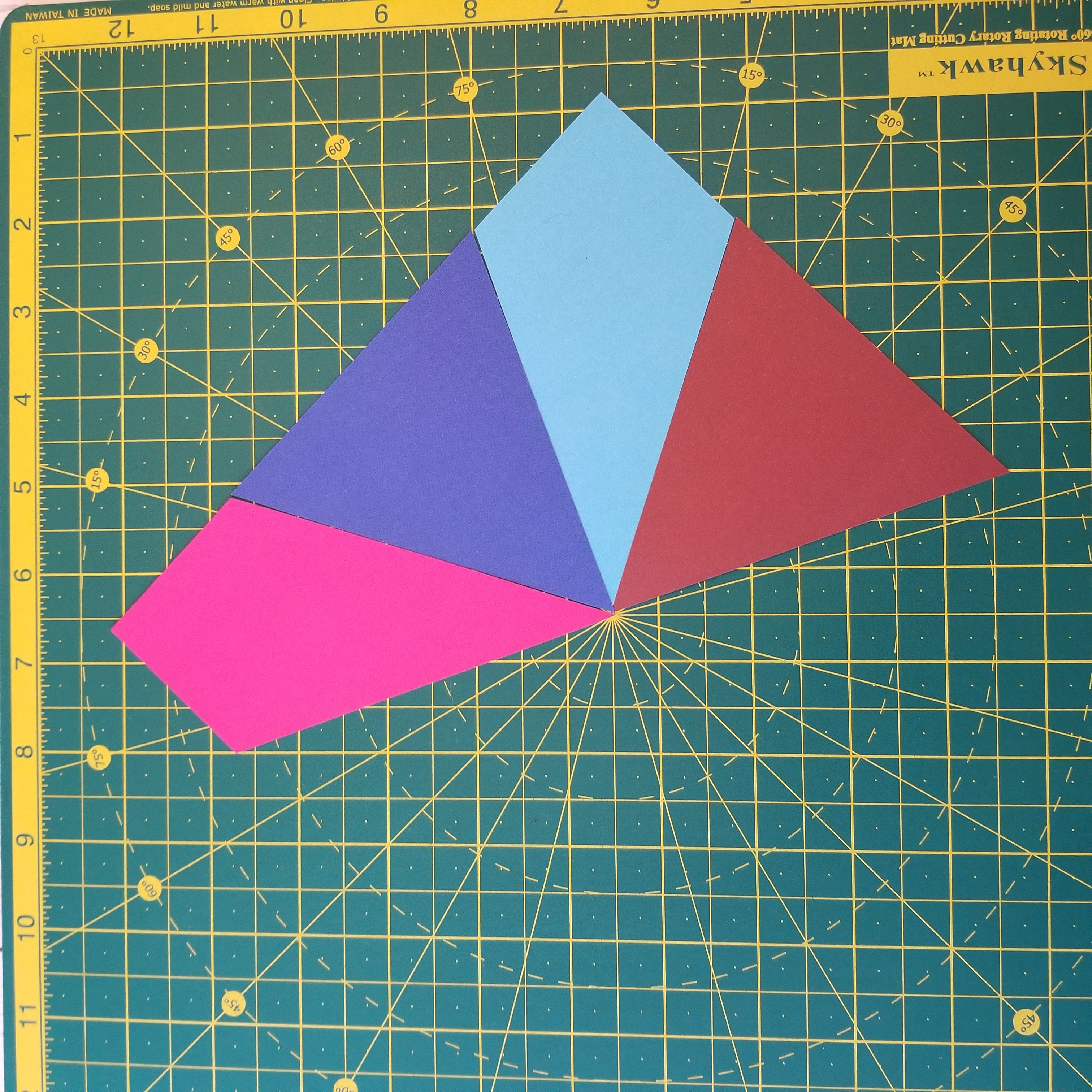 Half a quilt block made up of kite shapes and triangles on self healing cutting mat