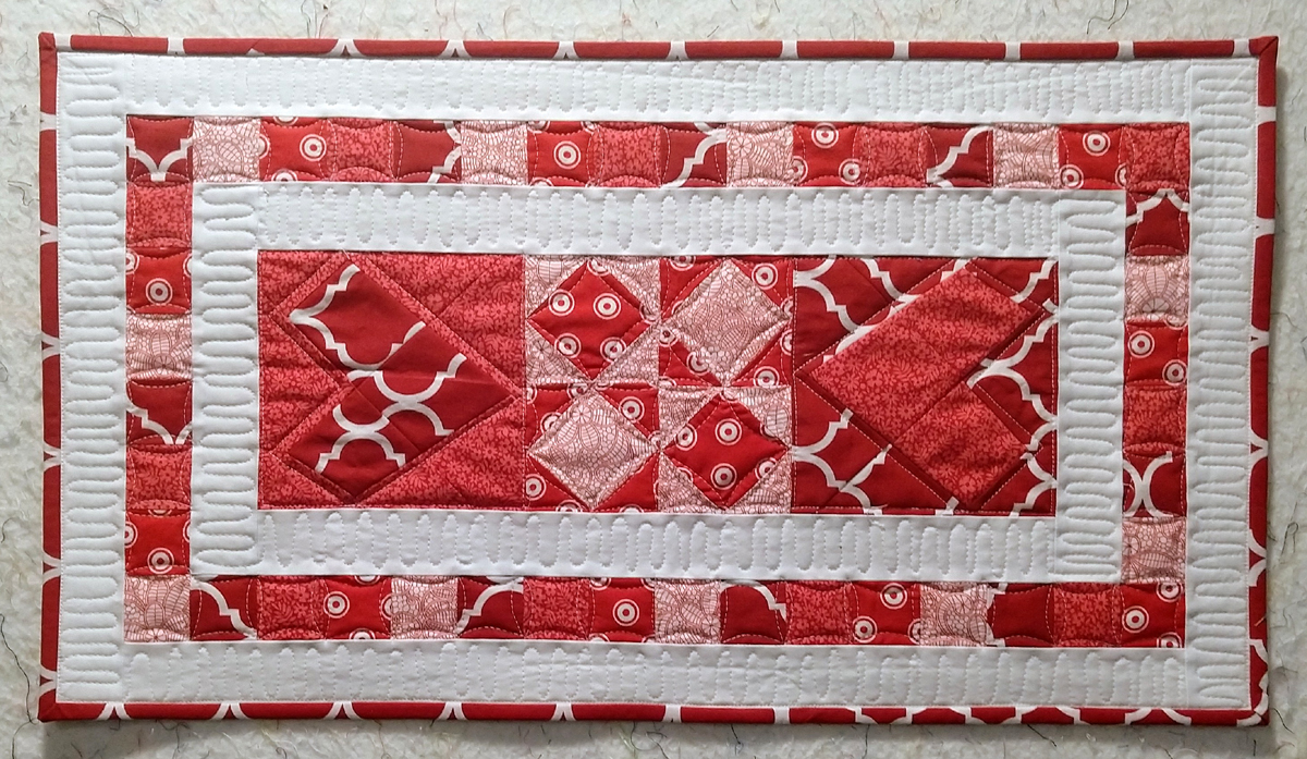 quilted red, white and pink heart table runner made with accuquilt wonky heart block