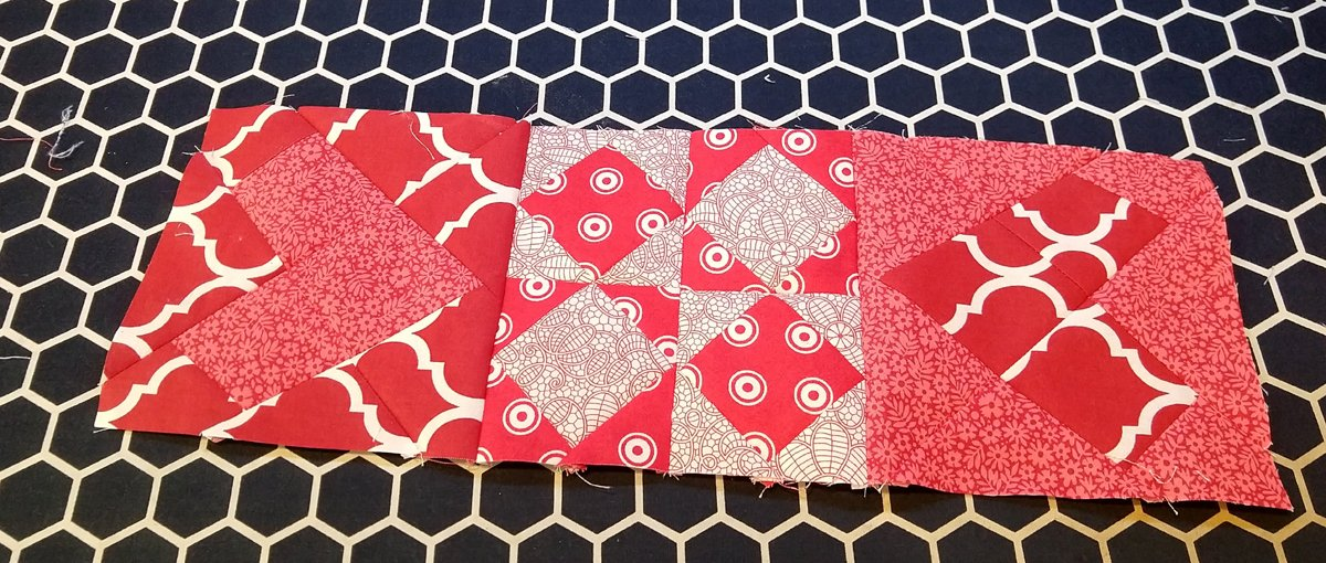 three red and white quilt blocks sewn together with wonky hearts on either side of a four patch of on point square blocks