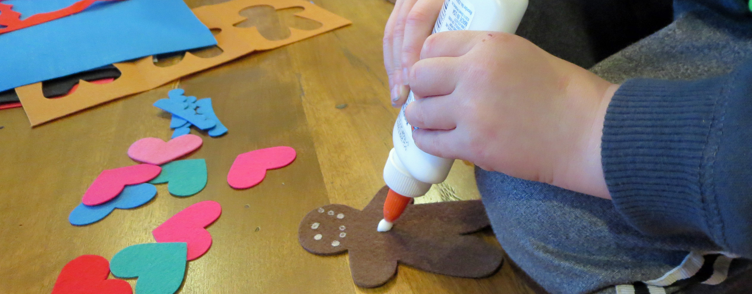 child placing glue dot on brown gingerbread man shape with a pile of felt hearts in pink, red and blues