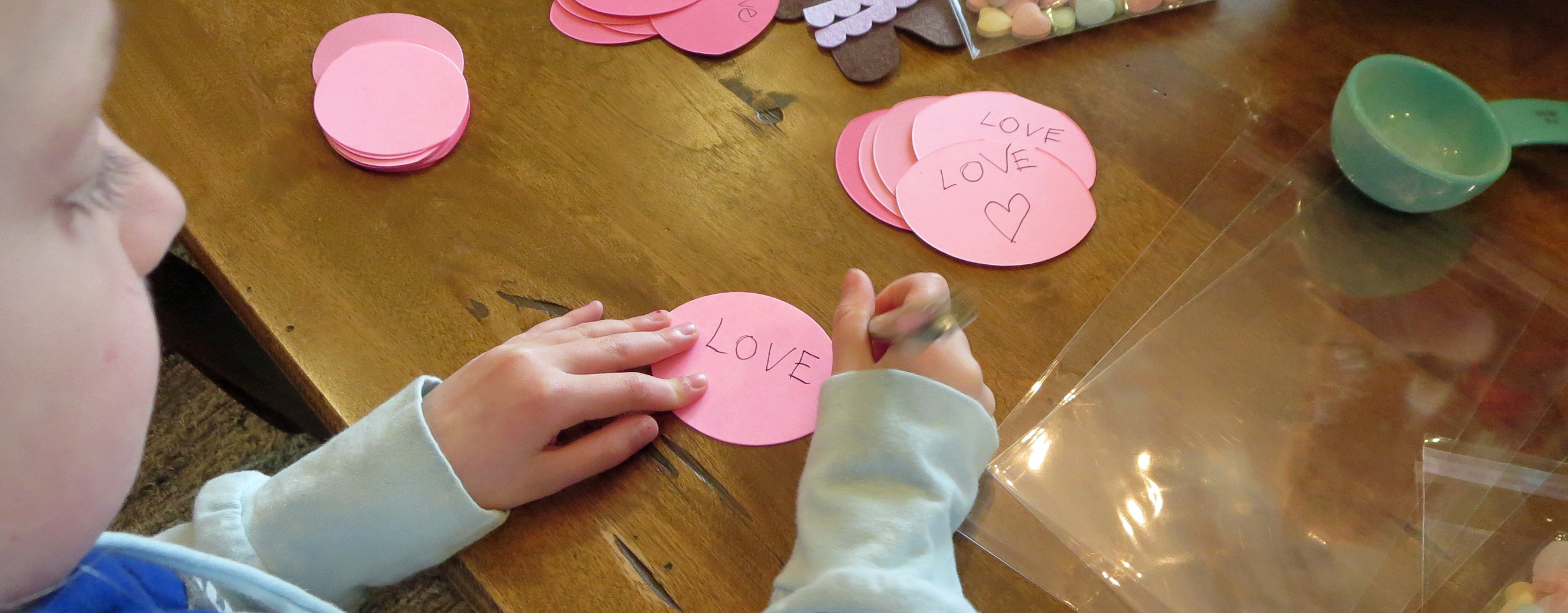 child writing the word love with a pen on pink paper oval on brown wooden table