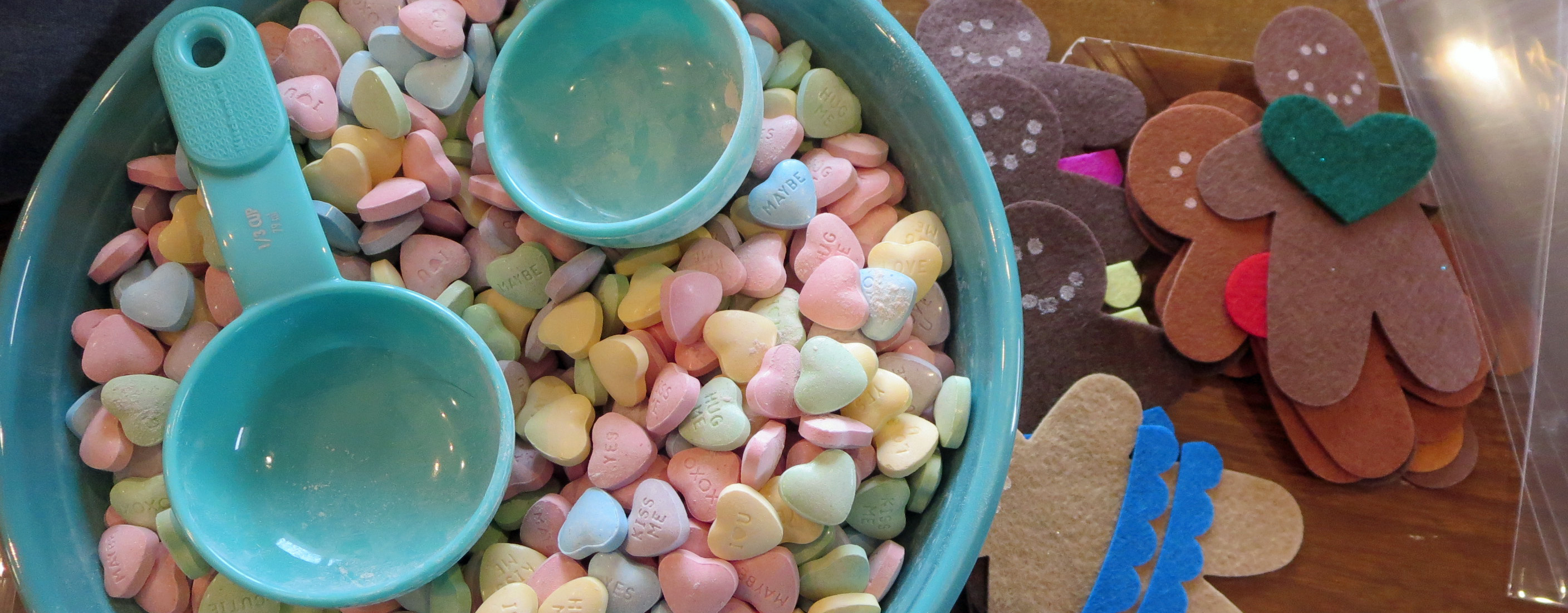 teal bowl of sweetheart candies next to brown felt gingerbread shapes with blue scallop dresses and green felt heart