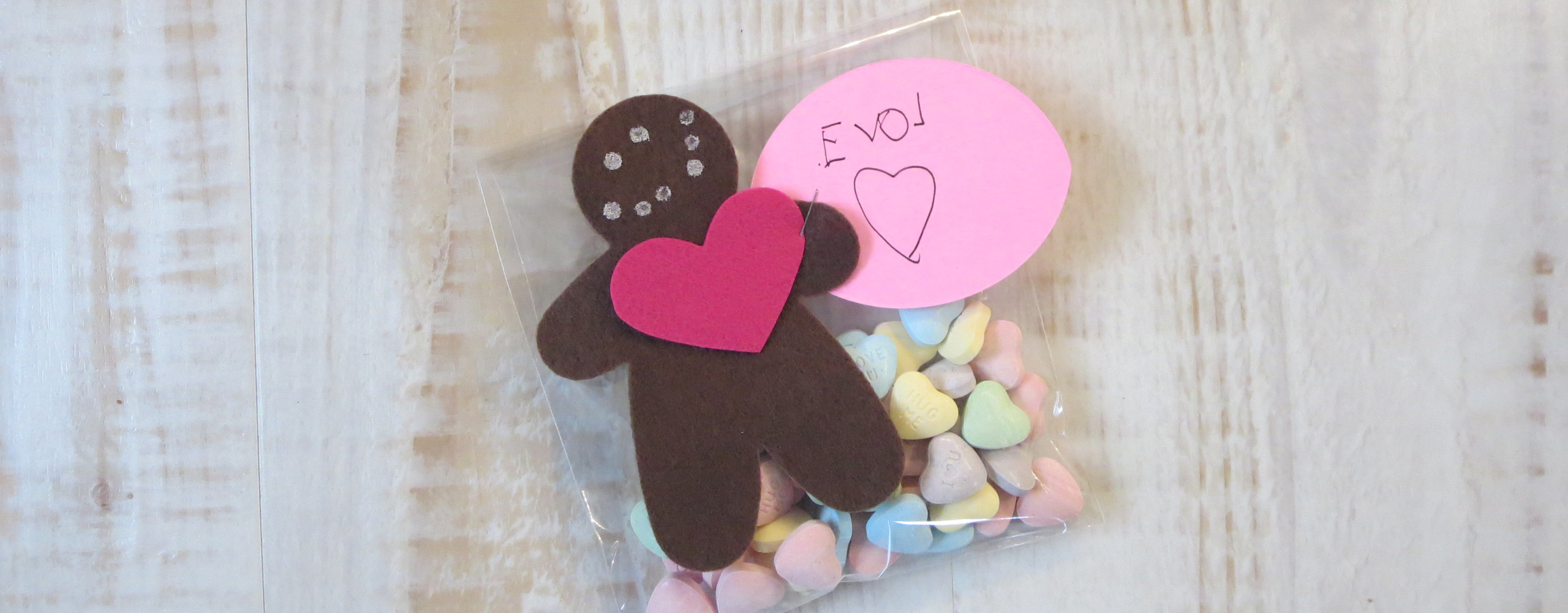 gift tag made with brown felt gingerbread man with a red felt heart on a bag of sweetheart candy on a whitewashed wood table