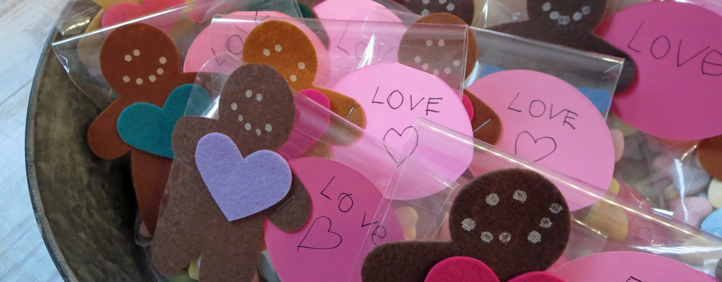 collection of felt gingerbread cookie shapes with felt hearts attached to bags of sweetheart candy