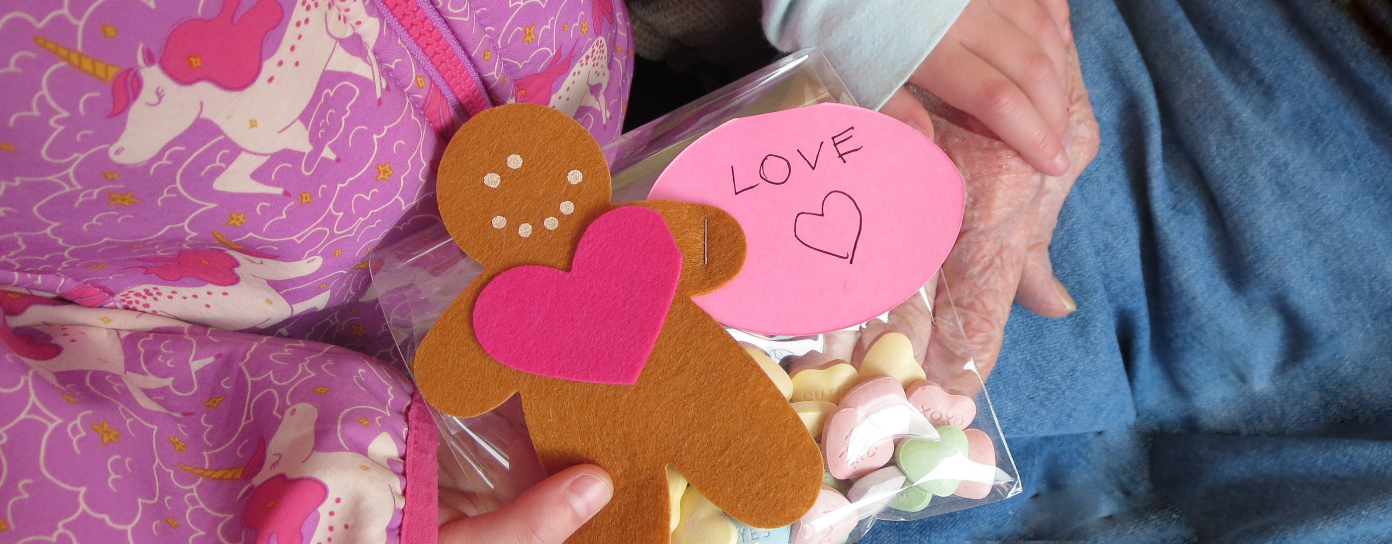 hands of a child giving bag of candy with felt gingerbread cookie shaped gift tag to hand of an older person
