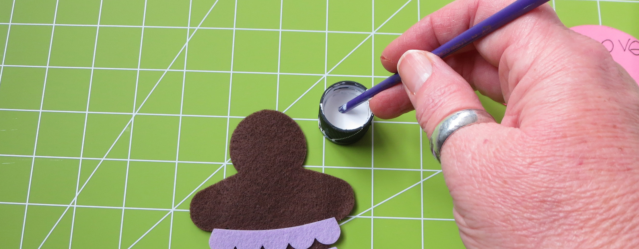 hand holding paint brush in white acrylic paint with brown felt gingerbread man on lime green self healing cutting mat