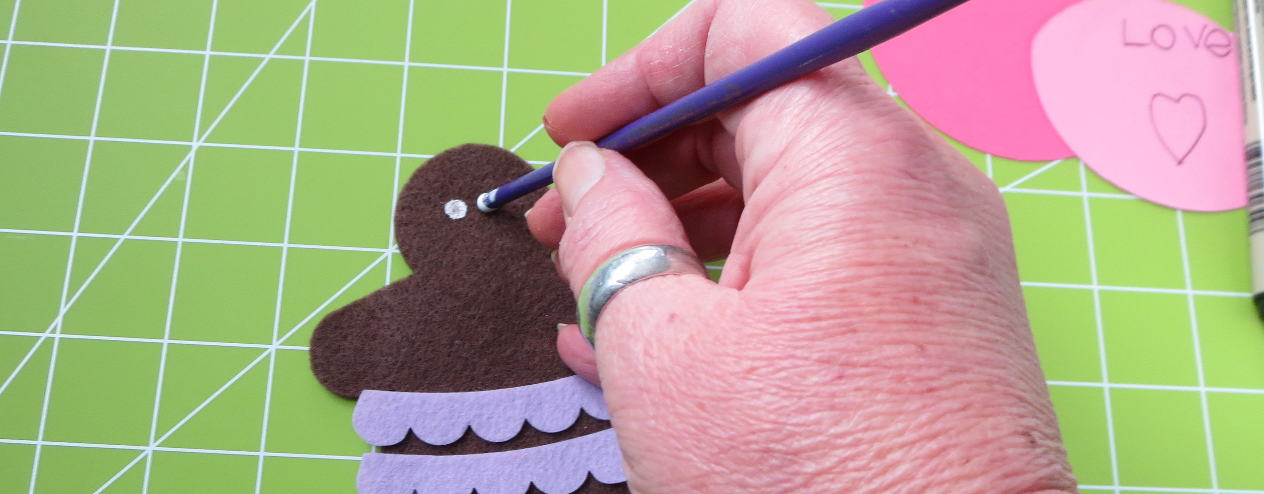 hand painting white eyes on a brown felt gingerbread man with white acrylic paint next to pink paper pieces