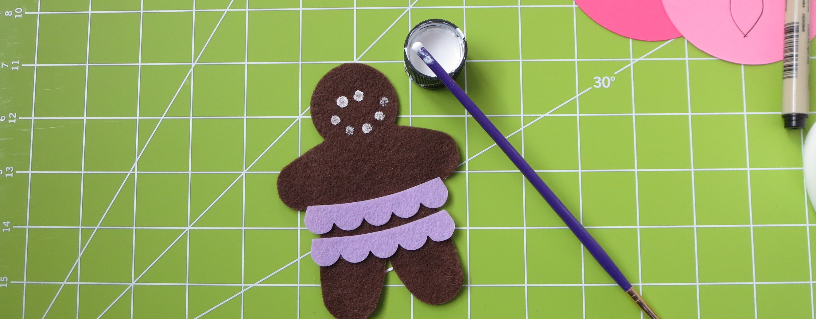 brown felt gingerbread man with lavender scalloped skirt with white paint circles for eyes and a smile next to paintbrush
